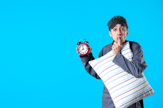 Front view young male in pajamas holding pillow and clocks on blue background dark nightmare bedroom insomnia night bed late sleep rest dreams