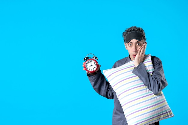 Front view young male in pajamas holding pillow and clocks on blue background nightmare dream bedroom insomnia sleep rest dark bed