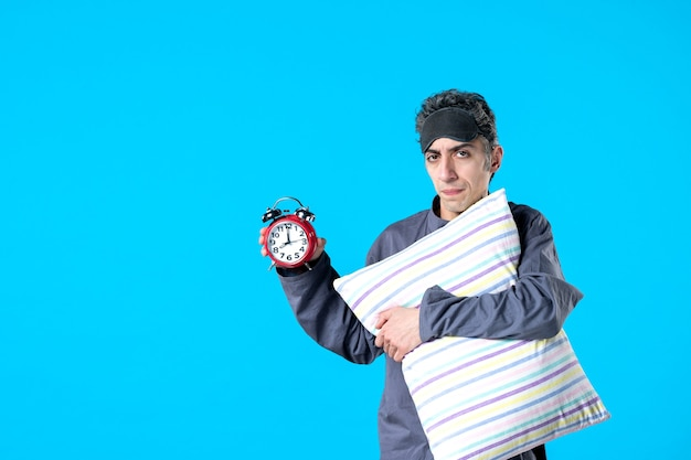 Front view young male in pajamas holding pillow and clocks on blue background nightmare dream bedroom insomnia sleep rest dark night bed