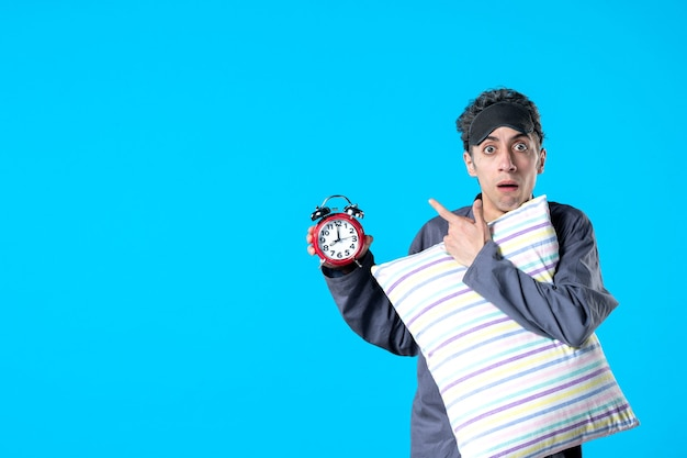 Front view young male in pajamas holding pillow and clocks on blue background nightmare dream bedroom insomnia sleep rest night bed