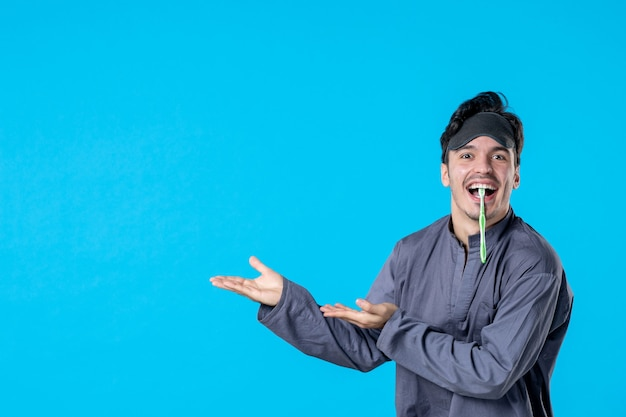 Front view young male in pajamas with toothbrush in his mouth on light blue background nightmare color pillow bed dreams wake dark human night