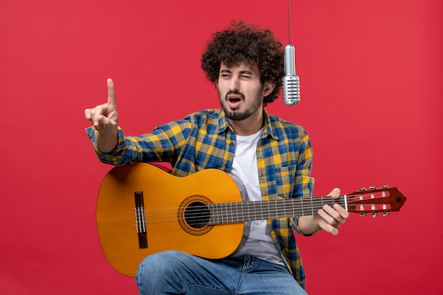 Вид спереди молодой мужчина играет на гитаре и поет на красном столе, выступление певца, концерт музыканта, живой цвет