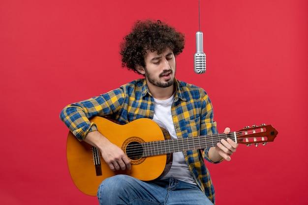 赤い壁のバンドの歌手のライブパフォーマンスミュージシャンコンサートカラーでギターを弾く正面図若い男性