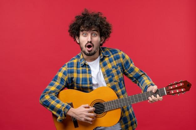 赤い壁のコンサートライブカラーバンド拍手音楽プレイミュージシャンでギターを弾く正面図若い男性