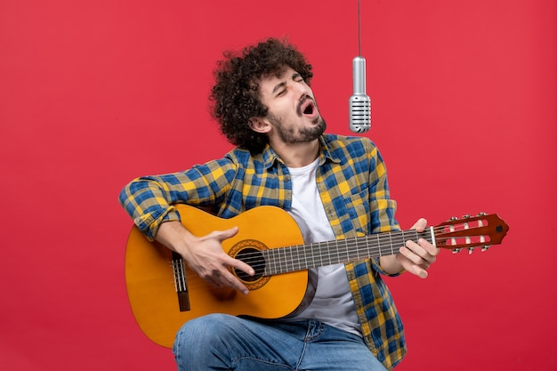 Front view young male playing guitar and singing on a red wall band singer performance musician concert live color