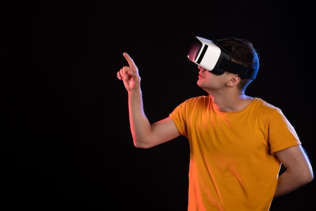 Front view of young male playing virtual reality on dark wall