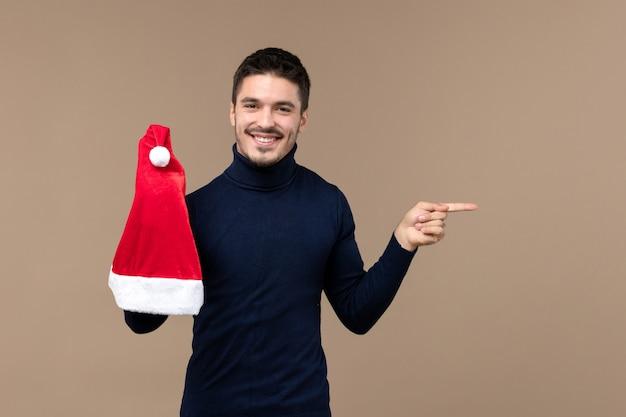 Вид спереди молодой самец играет с красной кепкой на коричневом фоне эмоции рождество новый год