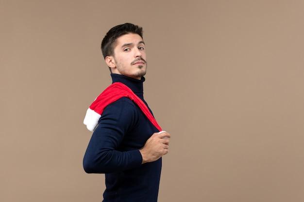 Вид спереди молодой мужчина играет с красной кепкой на коричневом фоне рождественские эмоции новый год