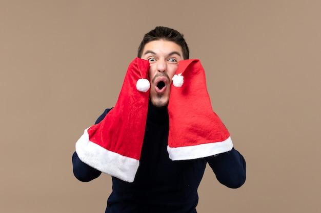 Вид спереди молодой самец, играющий с красными шапками на коричневом фоне, рождественские эмоции, новый год
