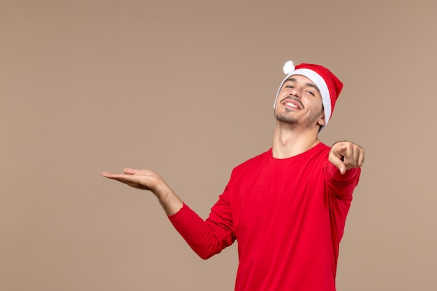 Front view young male pointing on brown background male color emotion holiday