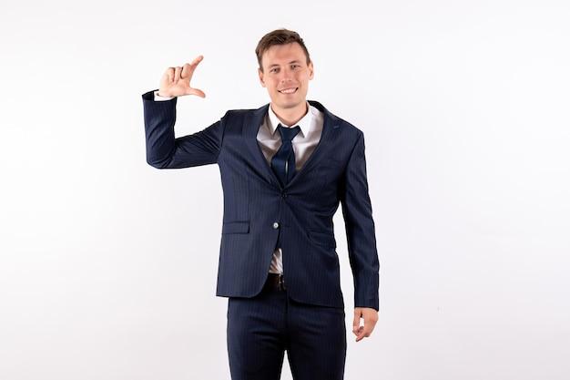 正面図白い背景の上の古典的な厳格なスーツでポーズをとって若い男性