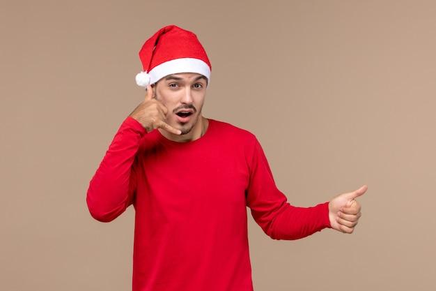 Вид спереди молодой мужчина позирует на коричневом фоне рождественский праздник эмоции