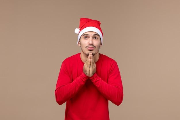 Вид спереди молодой мужчина молится на коричневом фоне рождественские эмоции праздник