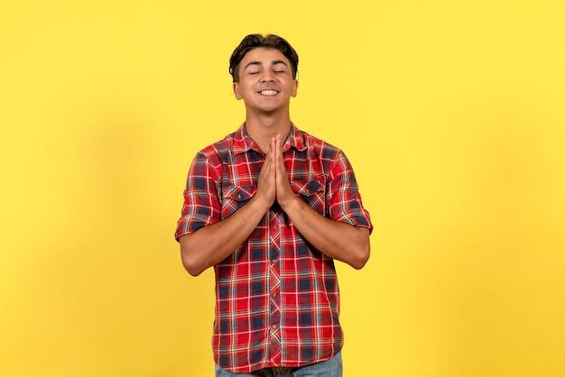 Vista frontale giovane maschio che prega su sfondo giallo
