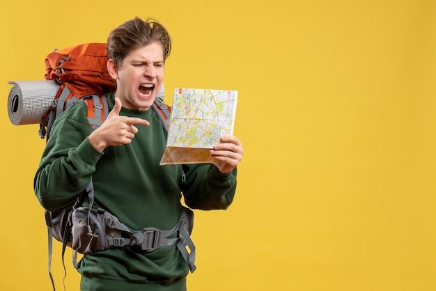 正面図の若い男性が地図を持ってハイキングの準備をしている