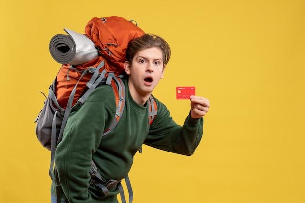 빨간 은행 카드를 들고 하이킹을 준비하는 전면보기 젊은 남성