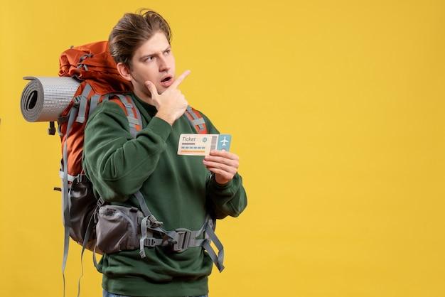 Вид спереди молодой мужчина готовится к походу с билетом