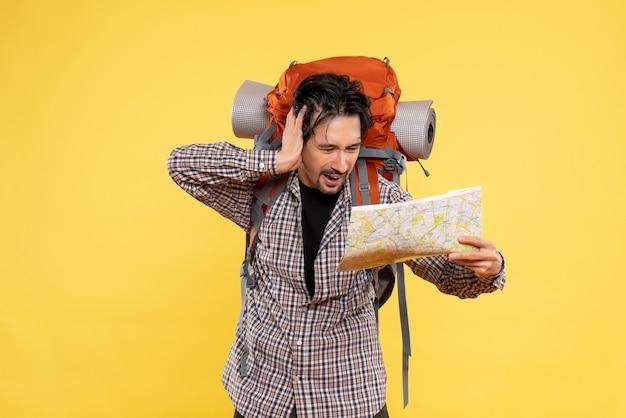 黄色の地図を観察してハイキングの準備をしている正面図若い男性
