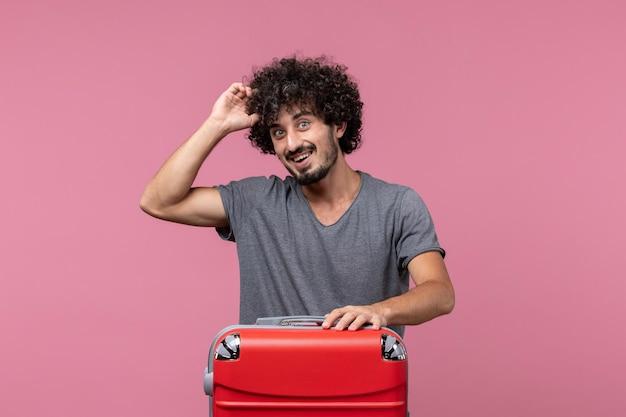 ピンクのスペースで飛行機旅行の準備をしている正面図若い男性