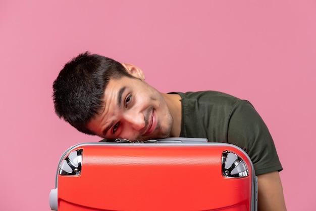 旅行の準備をしていて、ピンクの空間に疲れを感じている正面図若い男性