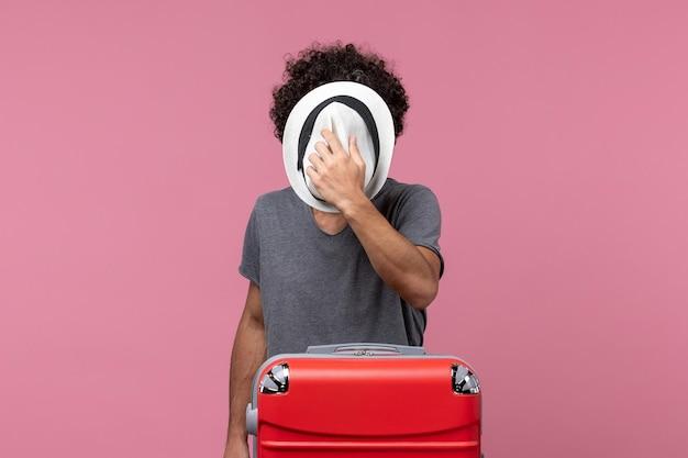 旅行の準備とピンクのスペースに帽子をかぶって正面図若い男性
