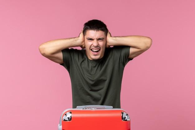 ピンクのスペースで彼の耳を閉じて旅行の準備をしている正面図若い男性