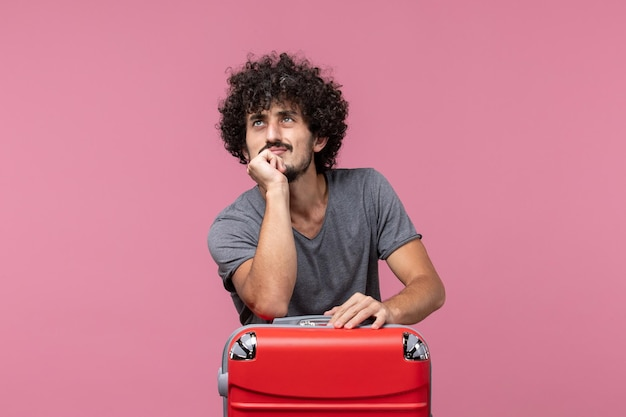 ピンクの机の上で旅行の準備をしている正面図若い男性