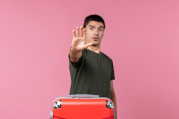 ピンクの空間で旅行の準備をしている正面図若い男性