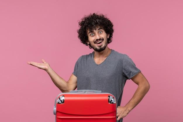 淡いピンクの空間で旅行の準備をしている正面図若い男性