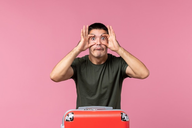 ピンクの空間に目を大きく開いて旅行の準備をしている正面図若い男性