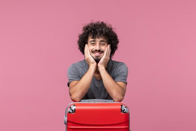 ピンクのスペースに笑顔のバッグと旅行の準備をしている若い男性の正面図