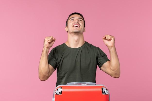 休暇の準備とピンクのスペースで幸せな気分の若い男性の正面図