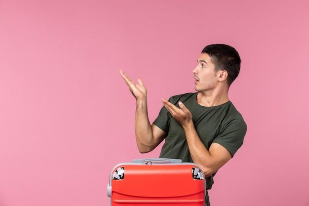Вид спереди молодой мужчина готовится к отпуску и смотрит на что-то на розовом пространстве