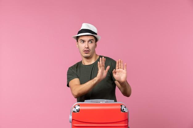 ピンクのスペースに帽子をかぶって休暇の準備をしている若い男性の正面図