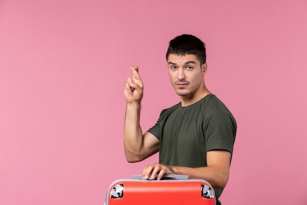 Вид спереди молодой самец готовится к отпуску, скрестив пальцы на розовом пространстве