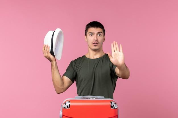 明るいピンクのスペースに帽子を保持して休暇の準備をしている正面図若い男性