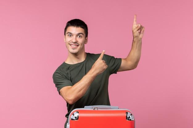 ピンクの空間で笑顔の休暇の準備をしている若い男性
