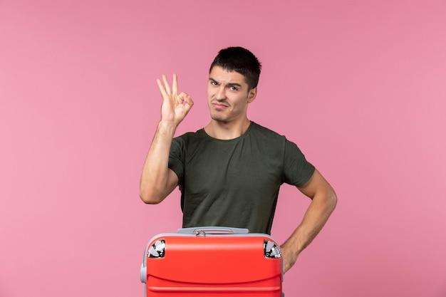 Вид спереди молодой самец готовится к отпуску с большой сумкой на розовом пространстве