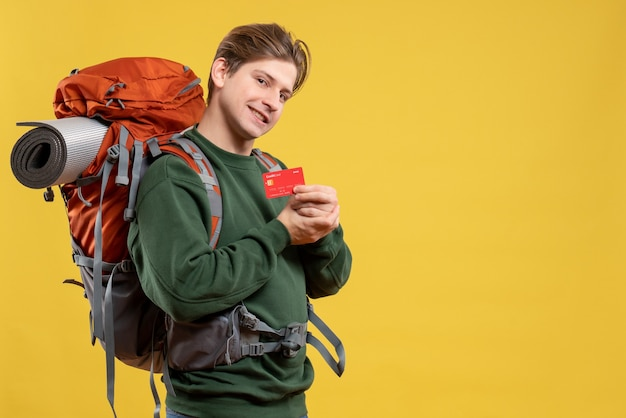 Front view young male preparing for hiking holding bank card