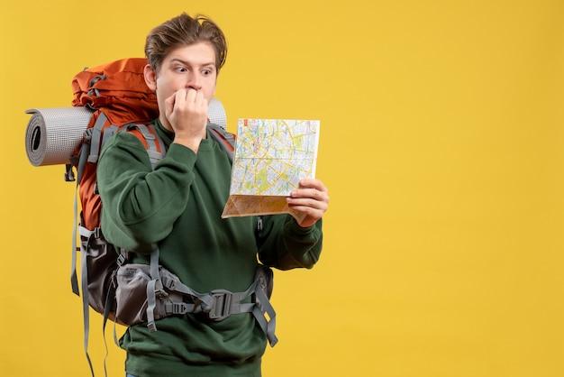 Vista frontale giovane maschio che si prepara per l'escursionismo tenendo la mappa spaventata