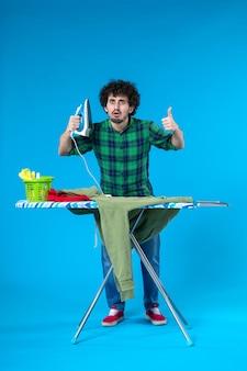 전면 보기 파란색 배경에 녹색 저지를 다림질할 준비를 하는 젊은 남성 깨끗한 세탁기 집 색상 인간