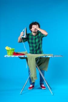 파란색 배경에 녹색 저지를 다림질할 준비를 하는 전면 보기 젊은 남성 깨끗한 세탁기 집안일 색상 인간