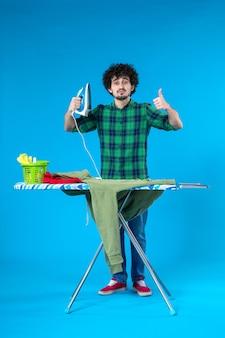 전면 보기 젊은 남성 파란색 배경에 녹색 저지를 다림질 준비 깨끗한 세탁기 집안일 집 색상 인간
