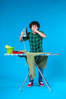 전면 보기 파란색 배경에 녹색 저지를 다림질할 준비를 하는 젊은 남성 깨끗한 세탁기 집안일 집 색상 인간