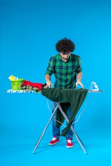 전면보기 젊은 남성 파란색 배경에 녹색 셔츠를 다림질 준비 깨끗한 세탁기 집안일 집 색상 인간