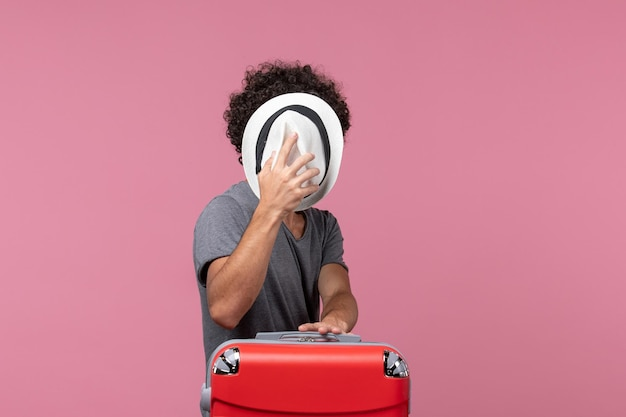 Front view young male preparing for trip and holding hat on pink desk