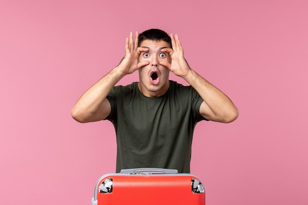 Giovane maschio di vista frontale che si prepara per il viaggio aprendo ampiamente gli occhi sullo spazio rosa