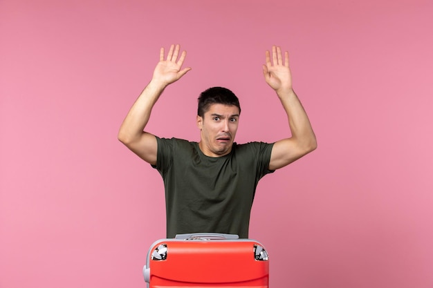 Front view young male preparing for trip with confused expression on pink space