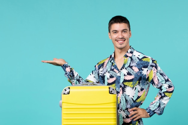 Front view of young male preparing for trip with his yellow bag and smiling on light-blue wall