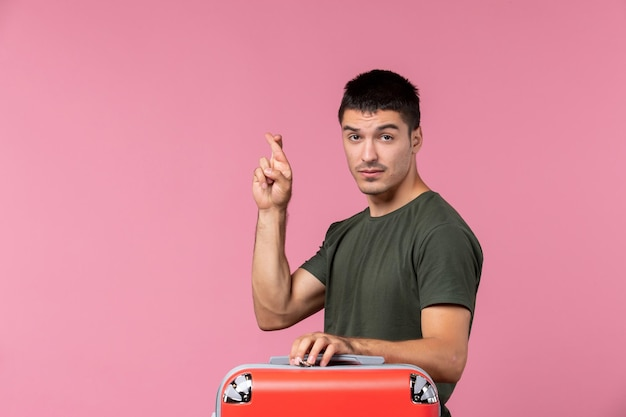 Front view young male preparing for vacation crossing his fingers on a pink space